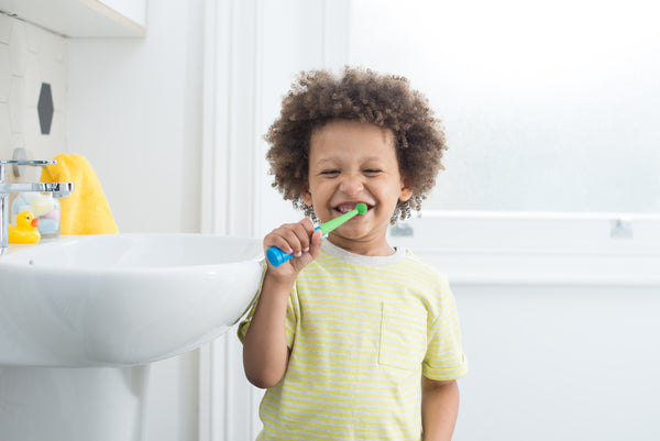 Happy kid brushes his teeth using Benjamin Brush and the pom pom head for toddlers