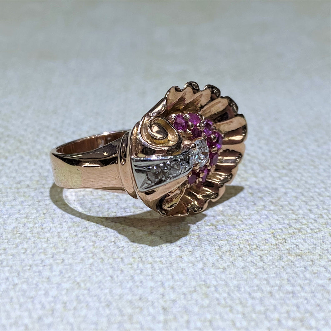 From our Estate Collection, this 14 Karat Rose Gold Ring features 10 ruby gemstones with .25dtw of accent diamonds with 14 karat rose gold fanning out for a unique design. The total weight of the ring is 11.1 Grams.  Finger size is 7.5  All weights are approximate
