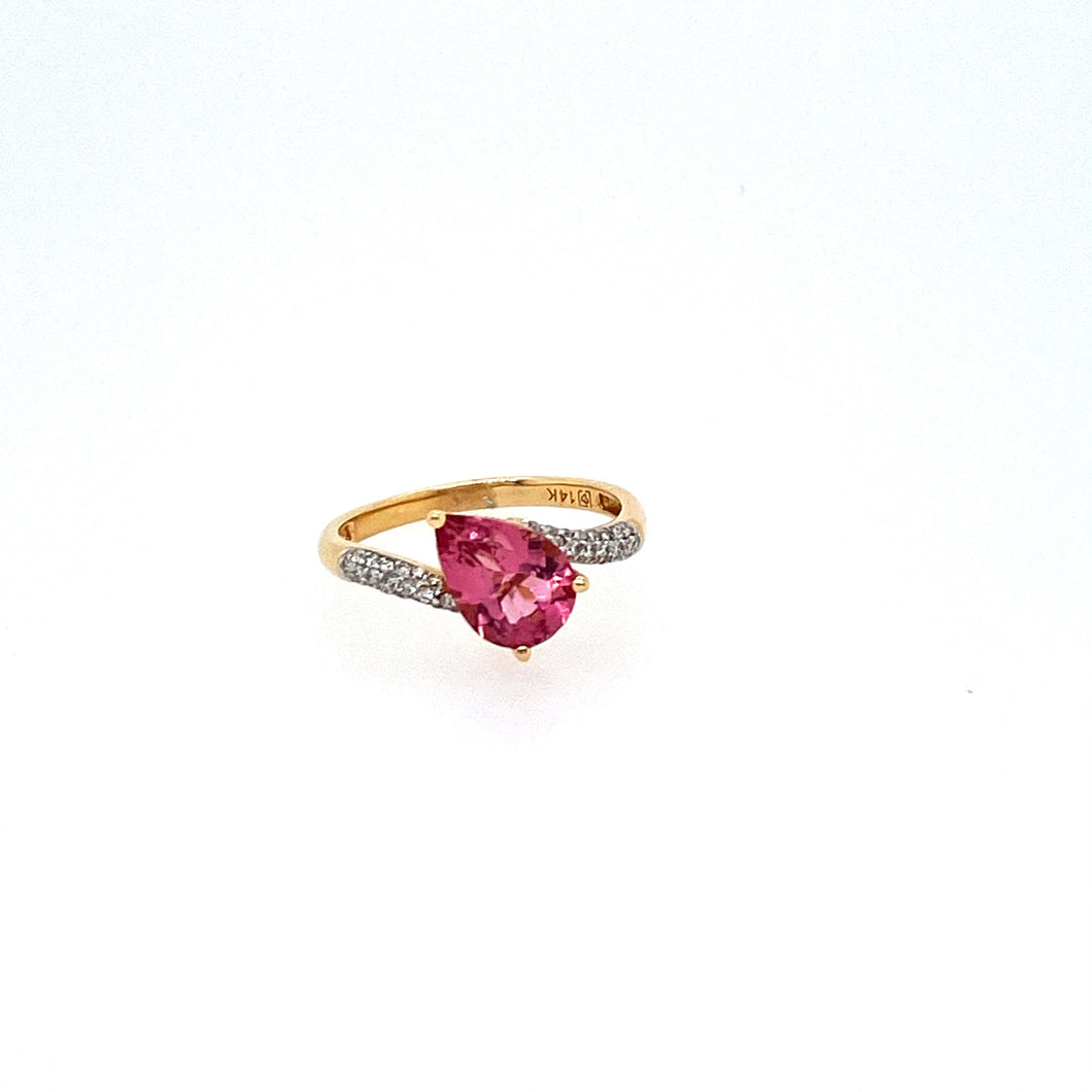 We Love the way this Pear Shaped Vibrant Pink Tourmaline Gemstone is set off balance to create a Classy Look. Set in 14 Karat Yellow gold, the Ring holds Shimmering Diamonds down the sides.  Total Diamond Weight is .18dtw  Finger Size 7