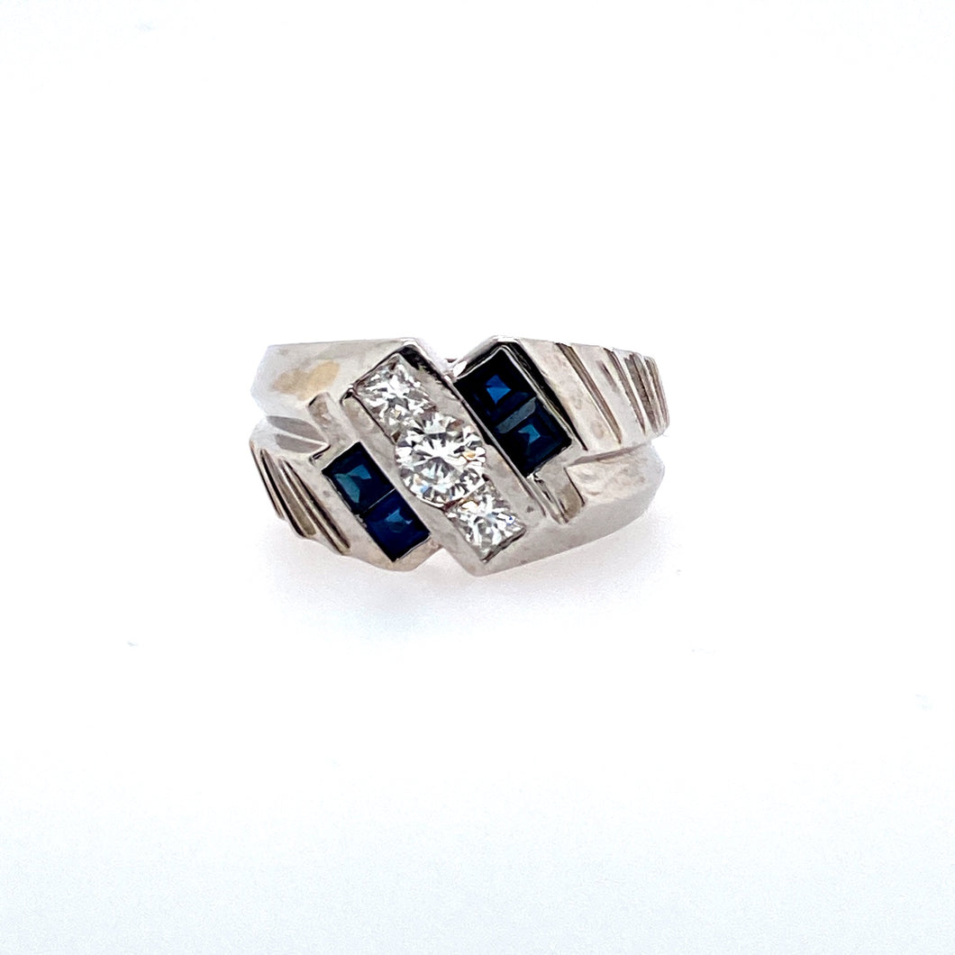 This 14 Karat White Gold Men's Estate Ring Features  One Round Diamond and Two Princess Cut Diamonds Sent into a Diagonal Setting and Two Princess Cut Blue Sapphire Gemstones set Side by Side on Each Side of the Diamonds.  The Ring has Ribbed Sides for a more masculine Look. Total Estimated Diamond Weight .73 Carat  Total Weight 9.5 Grams