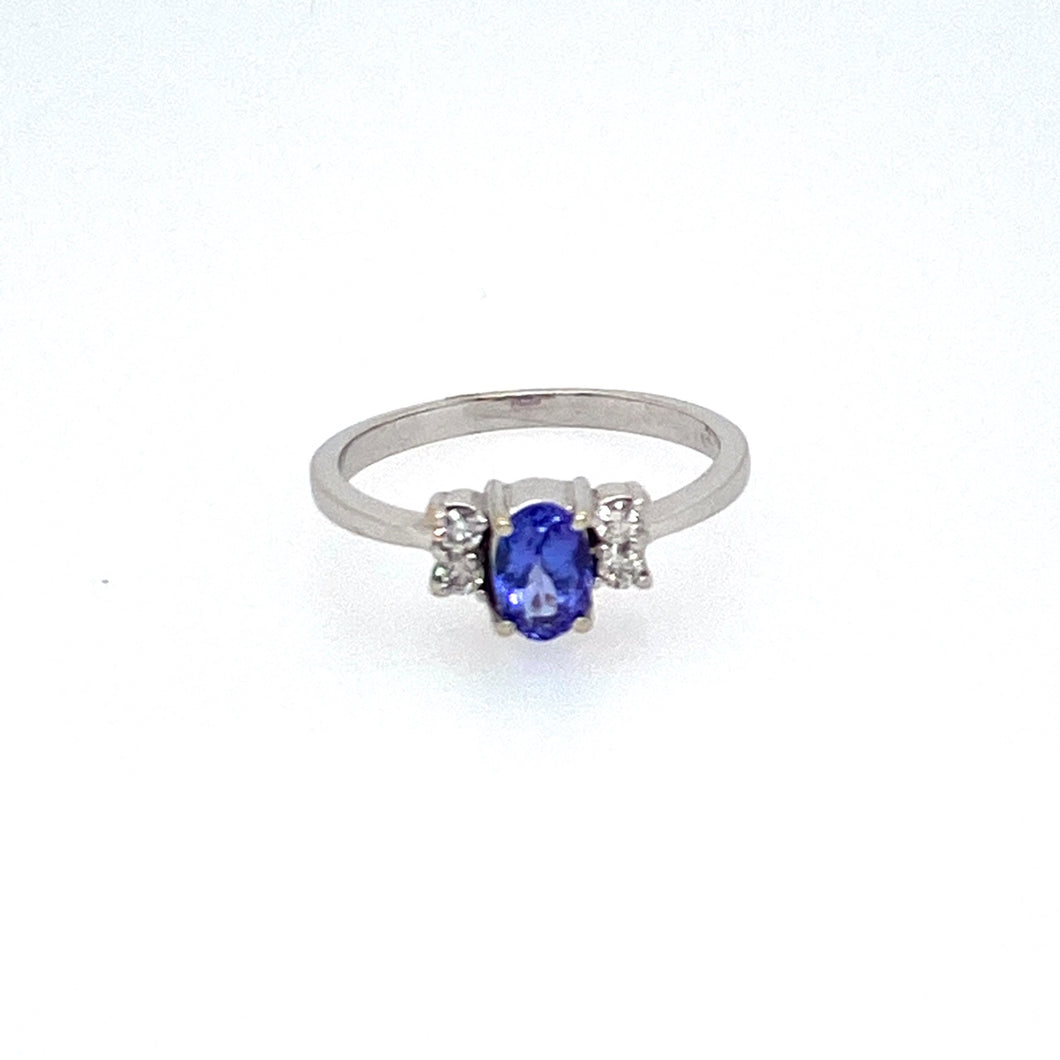 A Beautiful Bold Blue Oval Tanzanite Gemstone sets in the Center of this 14 Karat White Gold Estate Ring, with Two Diamonds set on Each Side of the Gemstone.  Total Weight 2.4 Grams  Finger Size 6.5