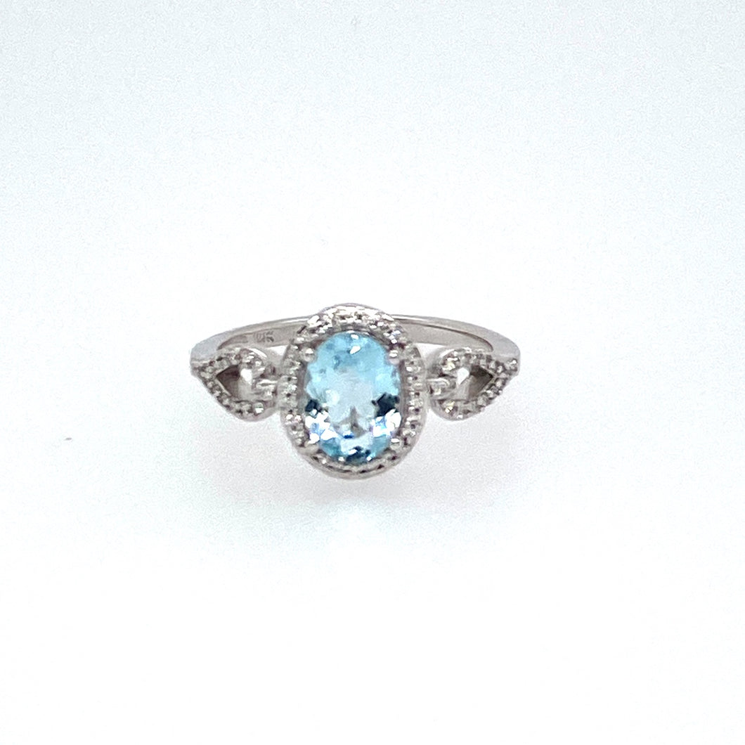 This 14 Karat White Gold Ring features a Cut out Pear Shaped Split Shank Design, Showcasing a 1.00 Carat Oval Shaped Light Blue Aquamarine Gemstone, Embellished with a Diamond Halo.   Total Diamond Weight .20dtw  Finger Size 7.25