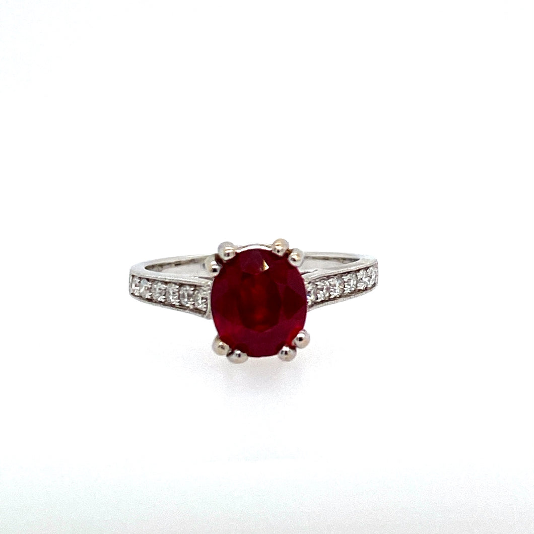 Simple but elegant, this 18 Karat White Gold ring Features a 2.15 Carat Oval Ruby Gemstone, secured with 4 Double Prongs, and Accented with .20ctw of Channel Set Round Diamonds.  Finger size 6.75