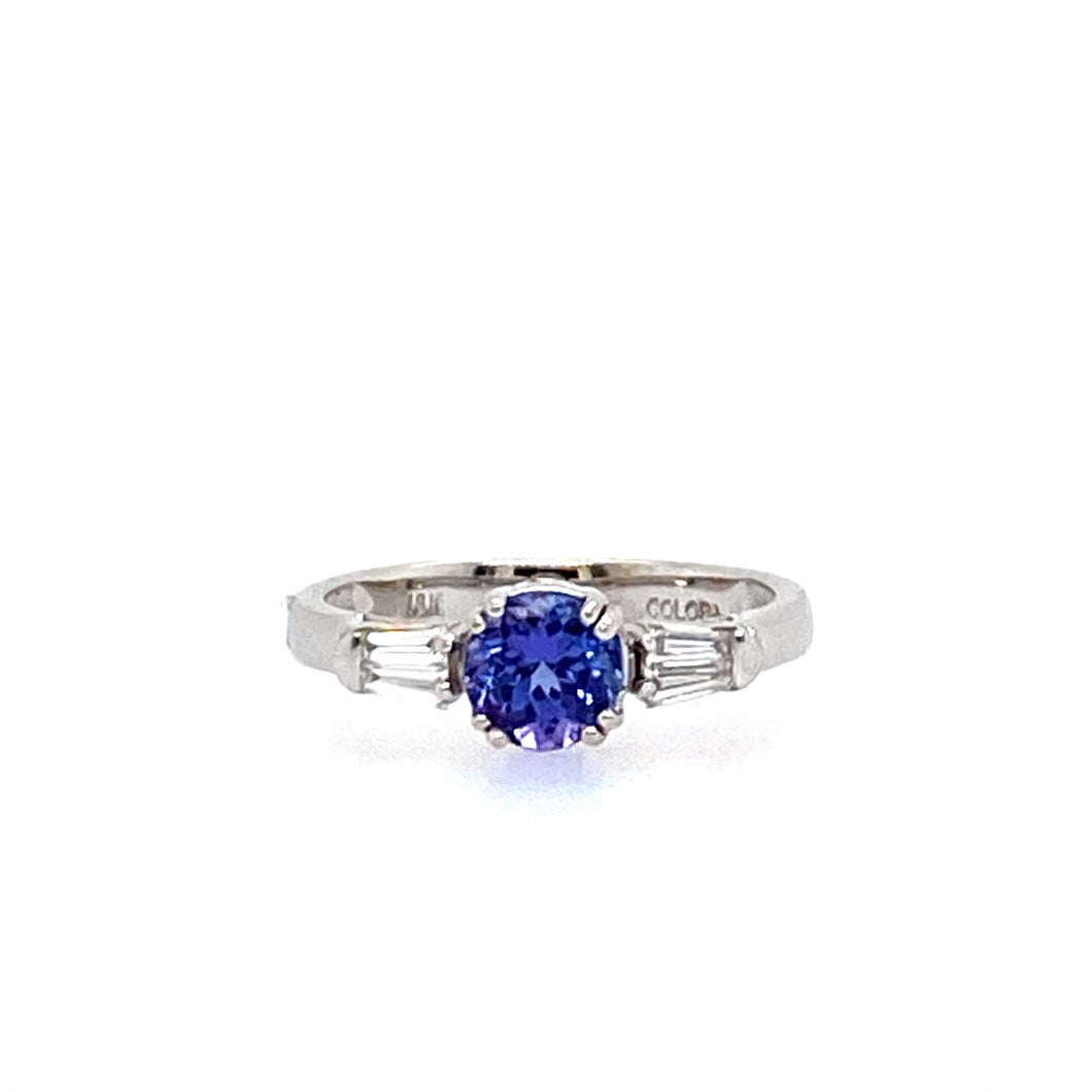 This Beautiful Round Blue-Purple .60 Carat Tanzanite Gemstone is Beautifully Set in Polished 18 Karat White Gold with a Tapered Baguette Diamond on Each Side.  Total Diamond Weight .25dtw  Total Weight 3.5 Grams  Finger Size 7