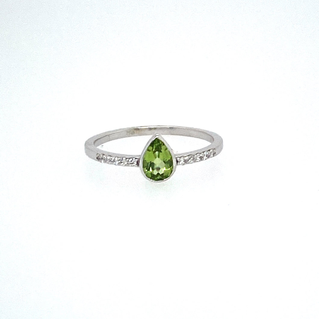 This Dainty 18 Karat White gold Ring Holds a Pear Shaped Bezel Set Peridot Gemstone with Accent Diamonds Down the Sides.  Finger Size 6.5
