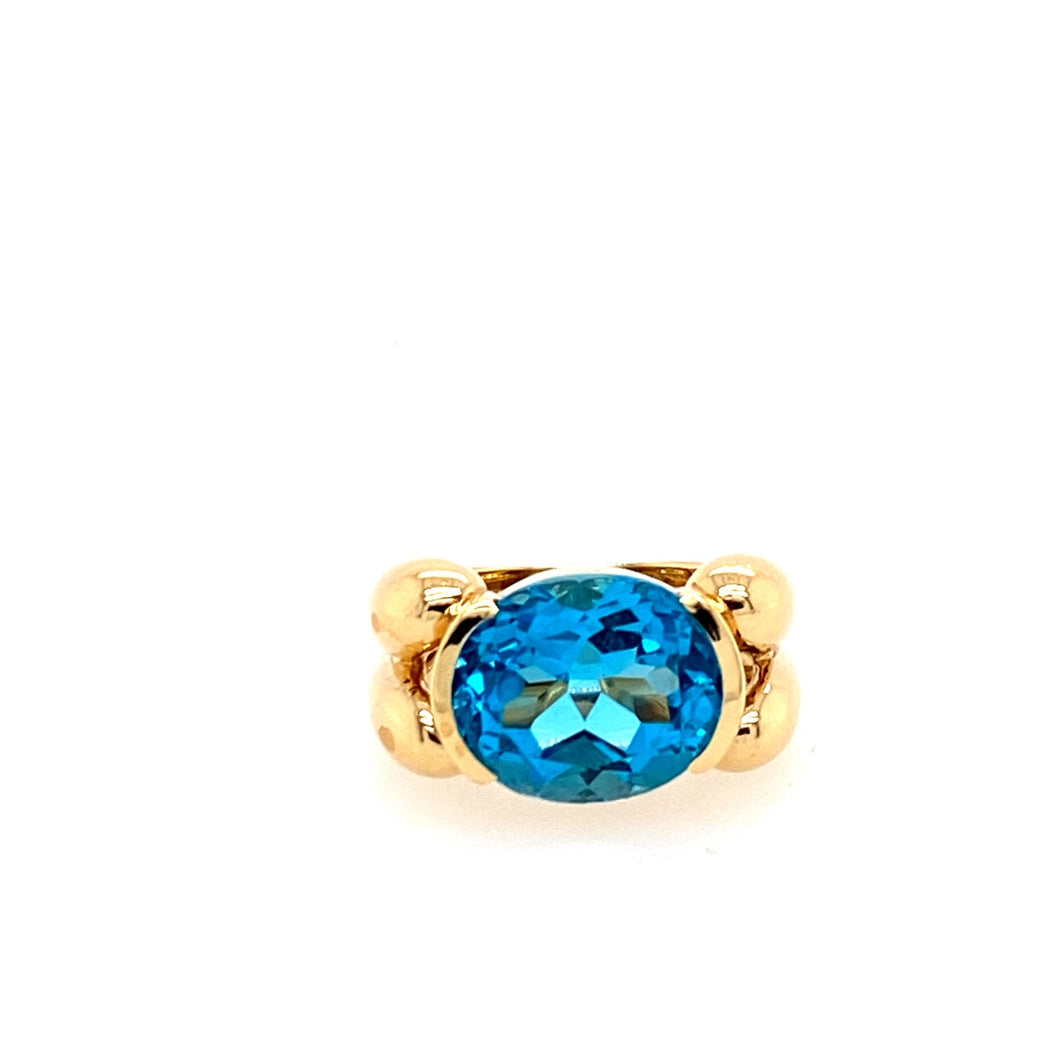 Semi Bezeled into this Beautifully Designed 14 Karat Yellow Gold ring is an Oval Faceted Blue Topaz Gemstone.   Finger Size 5.75