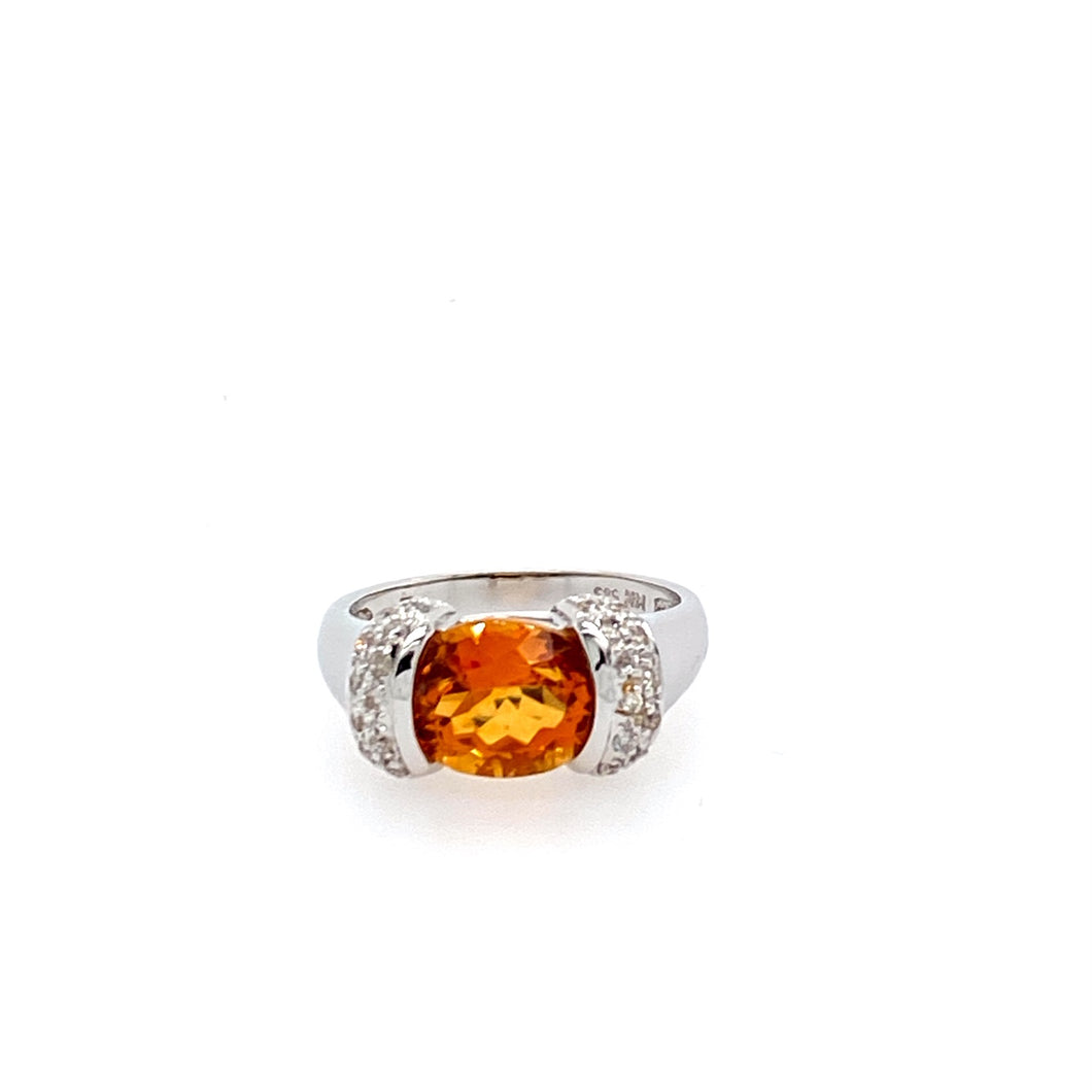 One of our favorite Citrine Rings, this 14 Karat White Gold Ring features an Oval Citrine Beautifully Faceted Gemstone  set Sideways with Diamond Accents.  The Vibrant Orange Color will Jazz up any outfit.  Finger Size 7