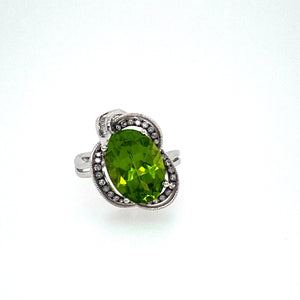 A Unique 14 Karat White Gold Designed Ring is Holding this 6.74 Carat Oval Peridot Gemstone with Some Sparkling Diamonds set around it.  Total Diamond Weight .29dtw  Total Weight 5.9 Grams  Finger Size 7