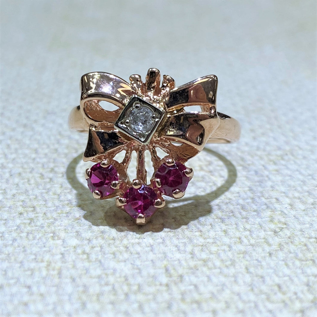This Dainty 14 Karat Rose Gold Ring from our Estate Collection features 3 Synthetic Ruby stones and One Diamond with a