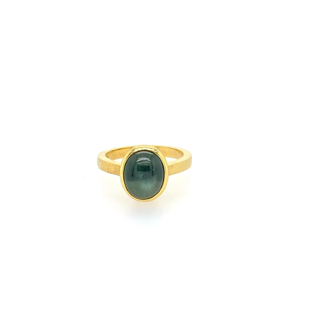 This Beautiful Oval Green Star Sapphire Gemstone is Bezel set in a Luxurious 18 Karat Yellow Gold Satin Finished Ring.  Total Weight is 6.7 Grams.   Size 6.5