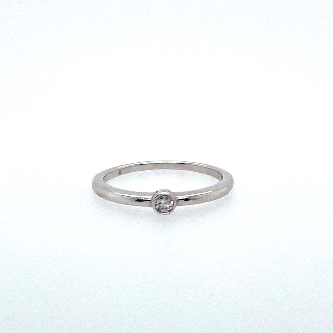This 14 Karat White Gold Promise Ring Features a .05 Carat Round diamond, Bezel set into the Center. Finger Size 6.5