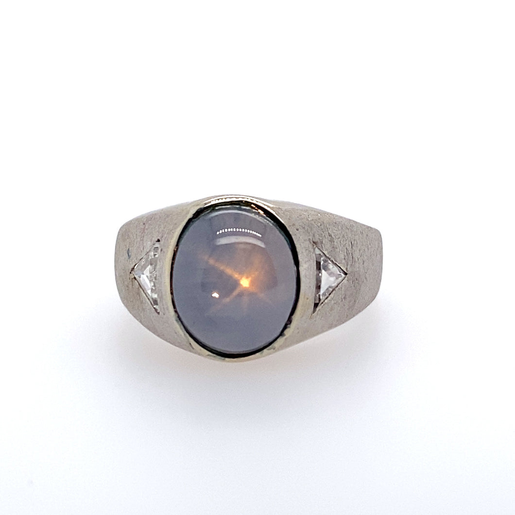 This Men's Estate Ring Features 14 Karat White gold with an Oval Gray Star Sapphire set into the Center. Set on Each Side of the Center is a Triangle Diamond.  the Sides of the Ring Feature a Satin Finish.  Finger Size 11.25  Total Weight 11.7 Grams