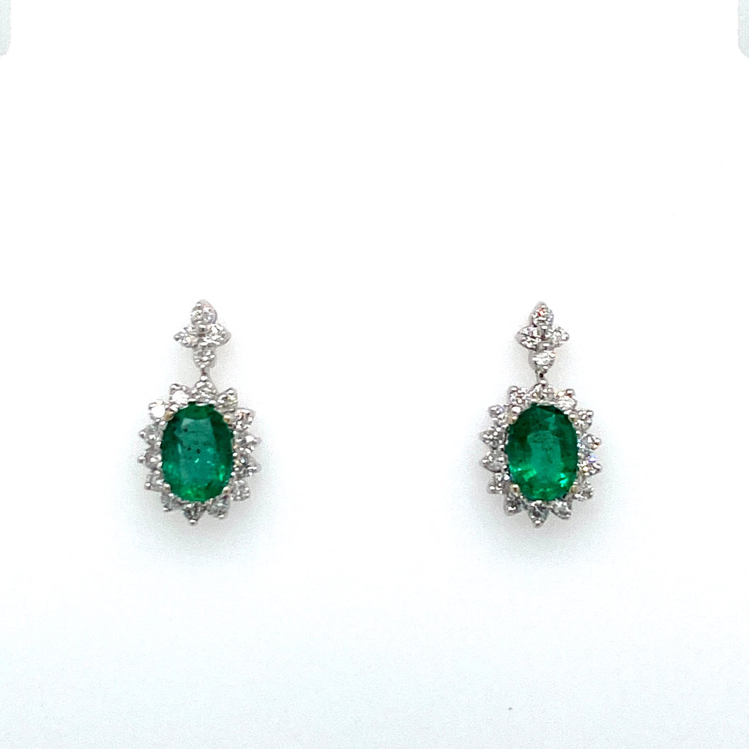 These 14 Karat White Gold Flower Like Earring Settings Feature an Oval Emerald with Diamonds Surrounding it and at the Top for an Elegant Look. The Earrings are Secured with Posts and Push on Backs.  Total Gemstone Weight 1.52 Carats  Total Diamond Weight .56 Carat