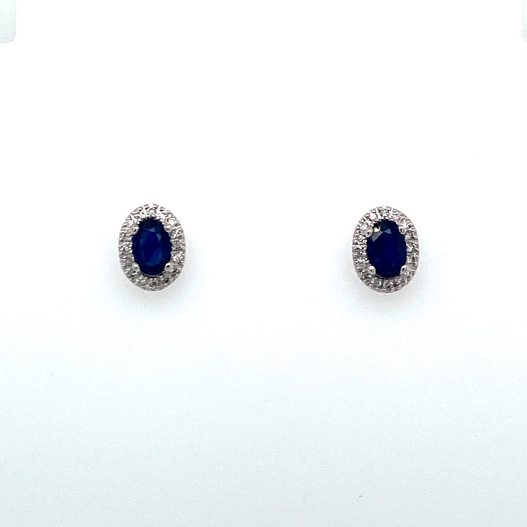 This Pretty Little Pair of 14 Karat White Gold Stud Earrings Feature an Oval Blue Sapphire Gemstone Embellished with a Diamond Halo.  The Earrings are Secured with Posts and Push on Backs.  Total Sapphire Gemstone Weight is 1.04 Carat