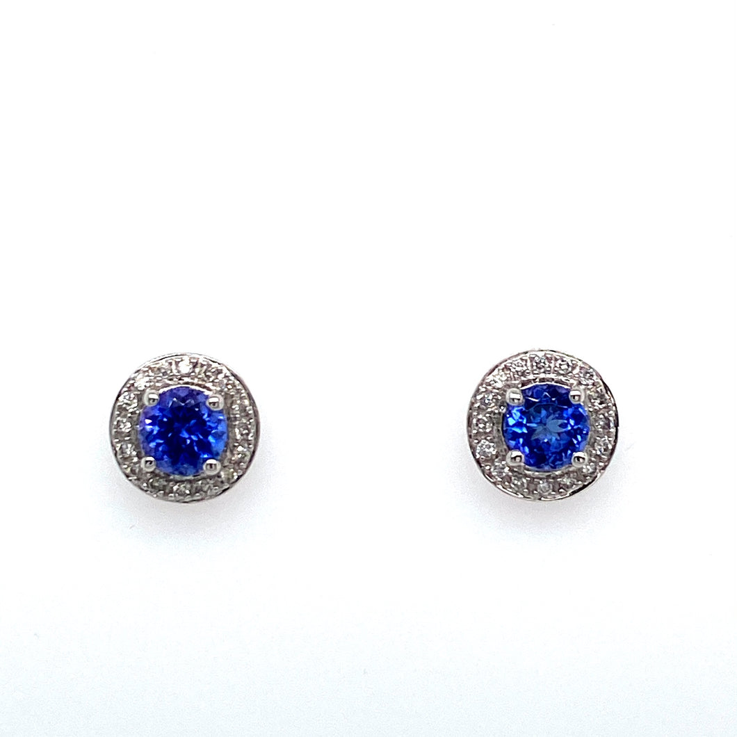 Magnificent Bold Blue Color best Describes these 14 Karat White Gold Round Tanzanite Gemstone Stud Earrings. Each Earring Features a 1 Carat Tanzanite Gemstone surrounded in a Round Diamond Halo Setting.  The Earrings are Secured with Posts and Push on Backs.  Total Gemstone Weight 2.05 Carats  Total Diamond Weight .25 Carat