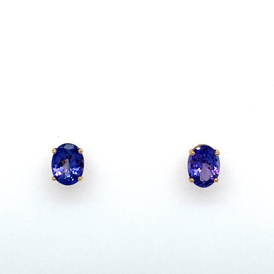 Each Earring is Set into 14 Karat Yellow Gold and Features a 1.25 Carat Oval Blue-Purple Tanzanite Gemstone. No Embellishing Needed with These Beauties, Secured with Posts and Push on Backs.  Total Gemstone Weight 2.50 Carats