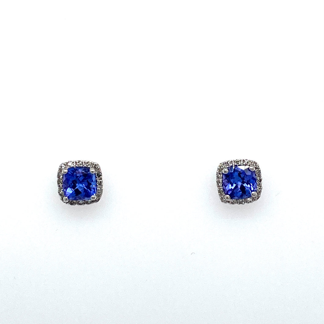 This Pair of 14 Karat White Gold Cushion Shape Earrings Feature a Cushion Cut Tanzanite Gemstone Surrounded by a Diamond Halo. the Earrings are Secured with Posts and Push on Backs.  Total Gemstone Weight 1.39 Carats  Total Diamond Weight .12 Carat