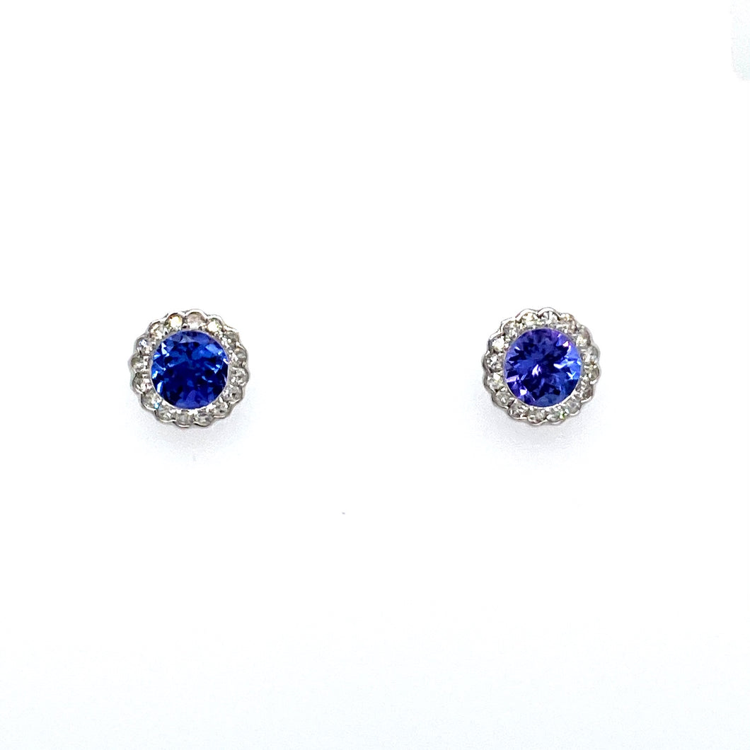 This Pair of 14 Karat White Gold Round Stud Earrings Feature a Rippled Setting with a Gorgeous Round Blue-Purple Tanzanite Gemstone set in the Center with a Diamond Halo. The Earrings are Secured with Posts and Push on Backs.  Total Gemstone Weight 1.11 Carats  Total Diamond Weight .23 Carat