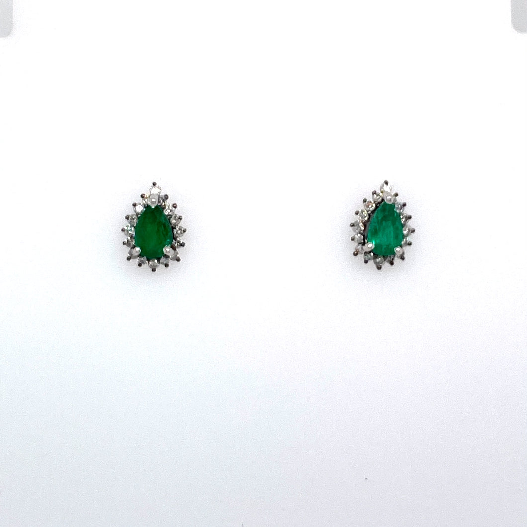 These Pear Shaped Emerald Gemstones are Set into Luxurious 18 Karat White Gold with a Diamond Halo Around the Gemstone.  The Earrings are Secured with Posts and Backs.  Total Gemstone Carat Weight .70 Carat  Total Diamond Weight .24 Carat