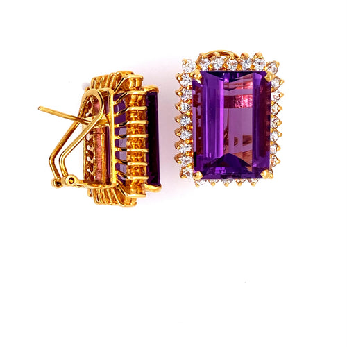 This Large Pair of Estate Earrings Feature a Emerald-Cut Amethyst Gemstone with a White Sapphire Halo around it.  The Heavy Earrings are Secured with Omega Backs.  Total Weight 19.6 Grams