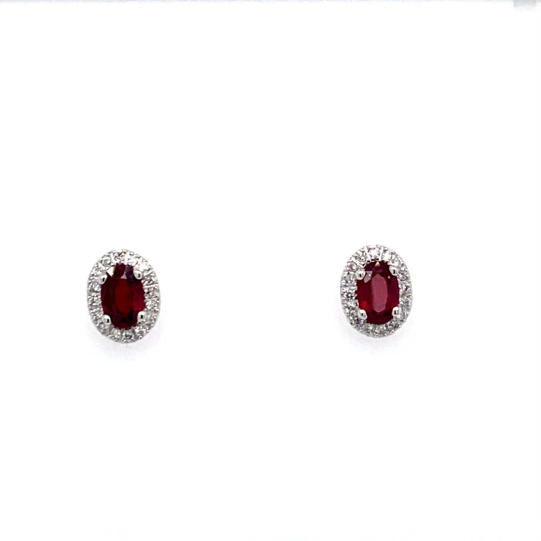 This Pair of 14 Karat White Gold Stud Earrings Feature a 1/2 Carat Red Ruby Gemstone, Accented with a Diamond Halo. The Earrings are Secured with Posts and Push on Backs.  Total Gemstone Weight 1.04 Carats
