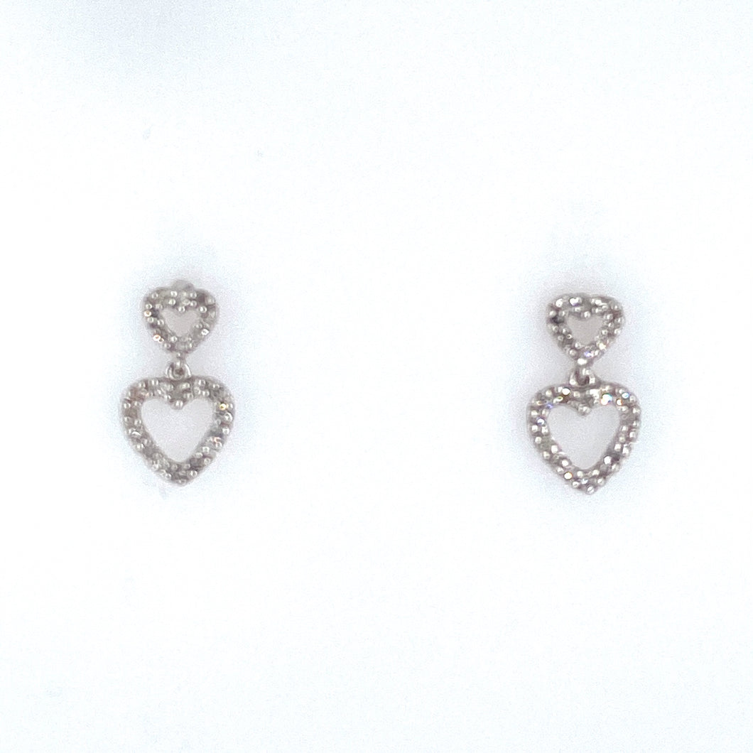This Pair of 14 Karat White Gold Earrings Feature an Open Small Heart with an Open Larger Heart at the Bottom, all Set with a Total of 44 White Diamonds. The Earrings are Secured with Posts and Backs . This is an Estate Piece