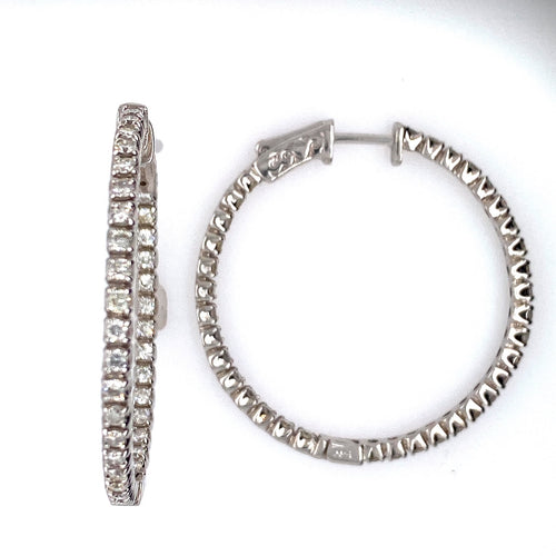 These 14 Karat White Gold Round Hoop Earrings Feature 1.40 Diamond Total Weight of Round Diamonds set Inside and Outside of the Earring. The Earrings Feature a Push Down Click in Closure.