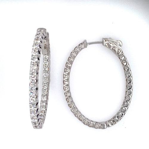 These 14 Karat White Gold Oval Hoop Earrings Feature 2.72 Carat Total Weight of White Sparkling Diamonds set inside and Outside of the Earring. The Hoops are Secured with a Push down click in Closure.
