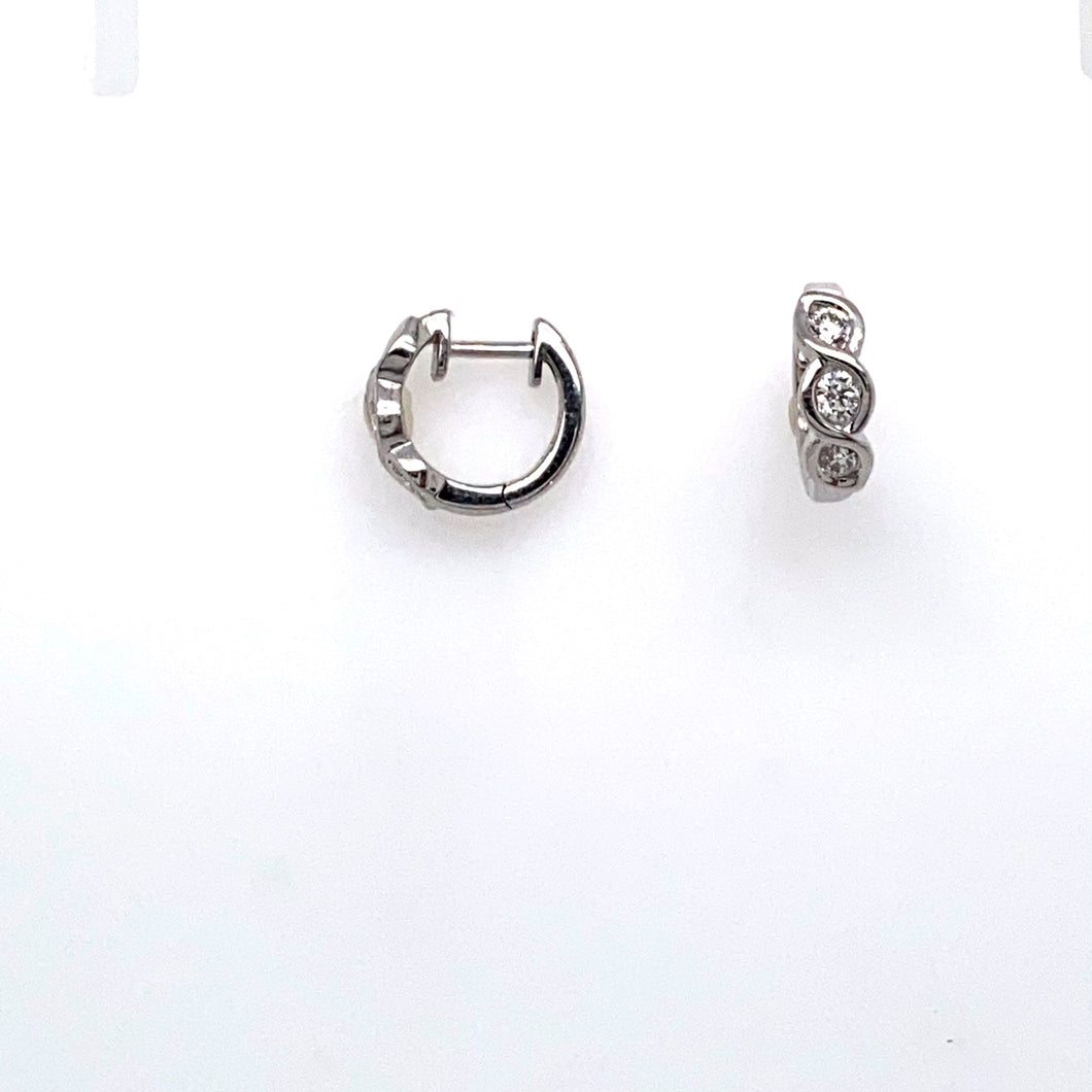 This Pair of Estate Round Huggie Style Earrings Feature 4 Diamonds each, Channel Set into a Swirl Setting. The Earrings art Secured with Click in Posts. Total Estimated Weight .25 Carat