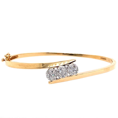 This 14 Karat Yellow Gold Hinged Bangle Bracelet features .30dtw of Diamonds in the center for a 3 stone look. It has added security with a safety 8  Total weight is 12.3 Grams