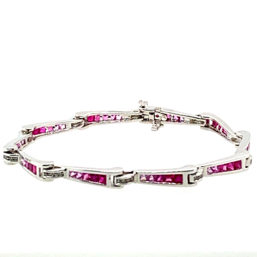 Show off your sophisticated style with this 18 Karat White Gold Bracelet. Each link graduates in color from Genuine Ruby gemstones to Pink Sapphire Gemstones totaling 3.00 total Carats. the bracelet holds even more sparkle with .33ctw of Diamonds. The hidden safety provides that extra security.  Length is 7