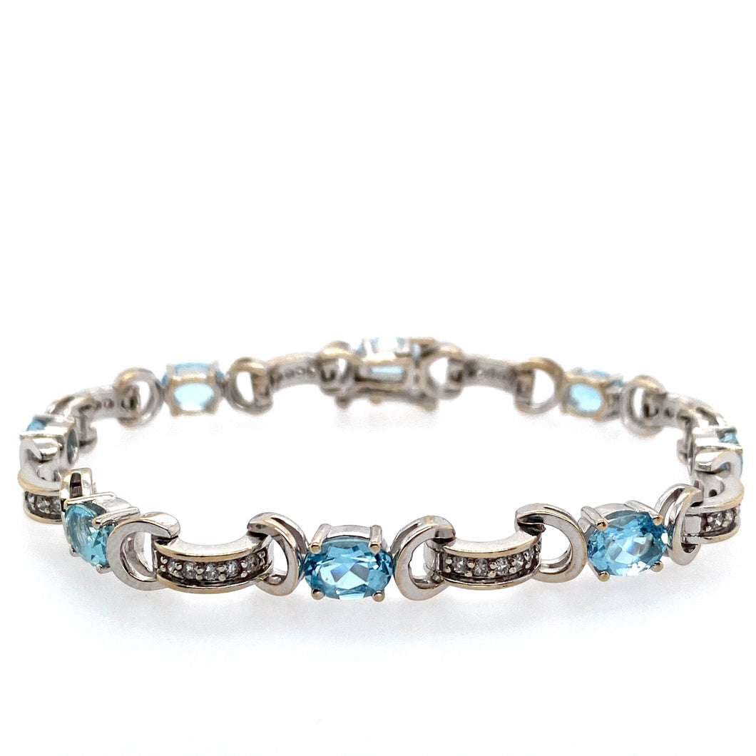 This Estate 14 Karat White Gold Bracelet Features Curved Links, Channel Set with Round Diamonds, Connected to 1/2 Moon Shaped Links.  In-between are Prong Set Oval Aquamarine Gemstones, Showcasing a Light Blue Color to the Bracelet.   Total Length is 7