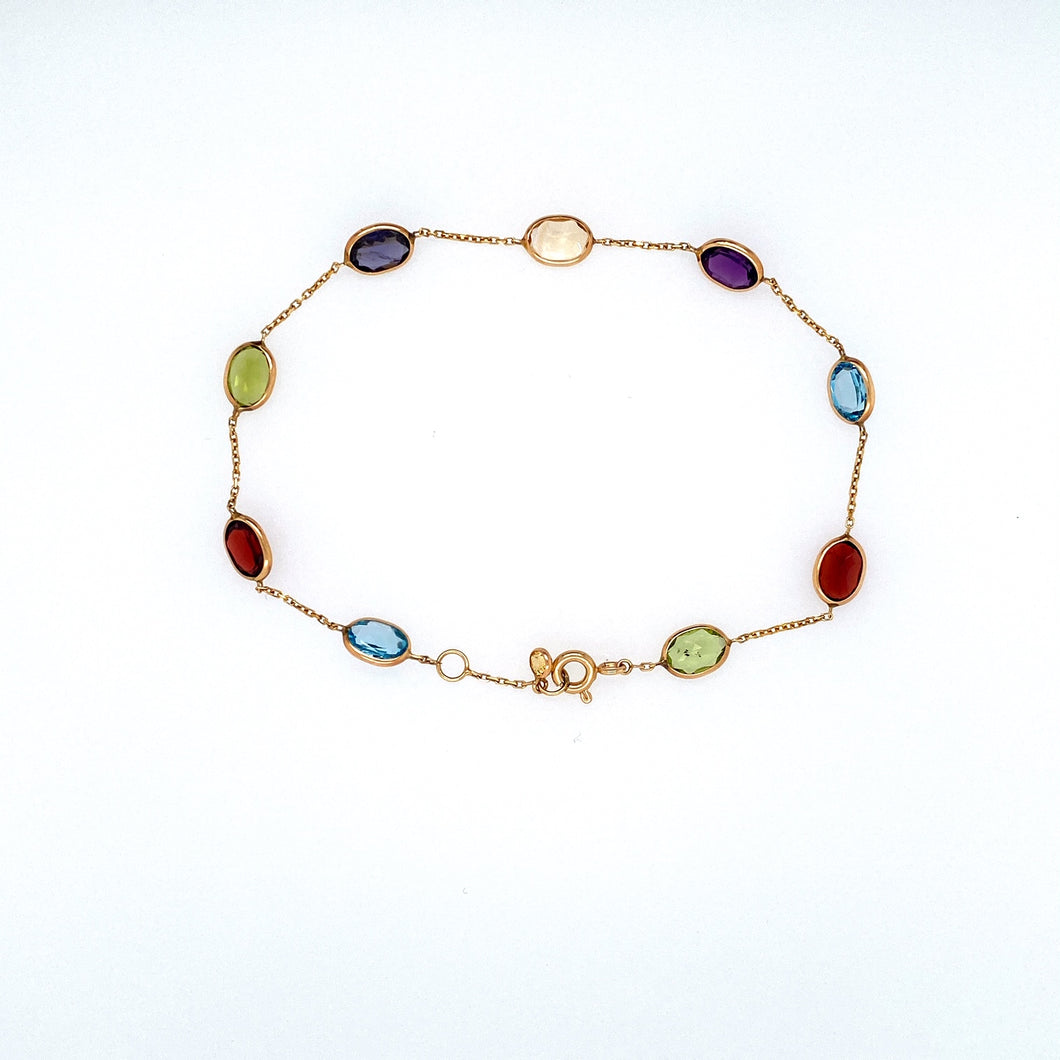 A Total Weight of 7.5 Carats of Semi Precious Gemstones Like Garnet, Amethyst, Peridot, and Blue Topaz, are Bezel set into 14 Karat Yellow Gold with a Link Chain In-between. The Bracelet is Secured with a Spring Ring Clasp.