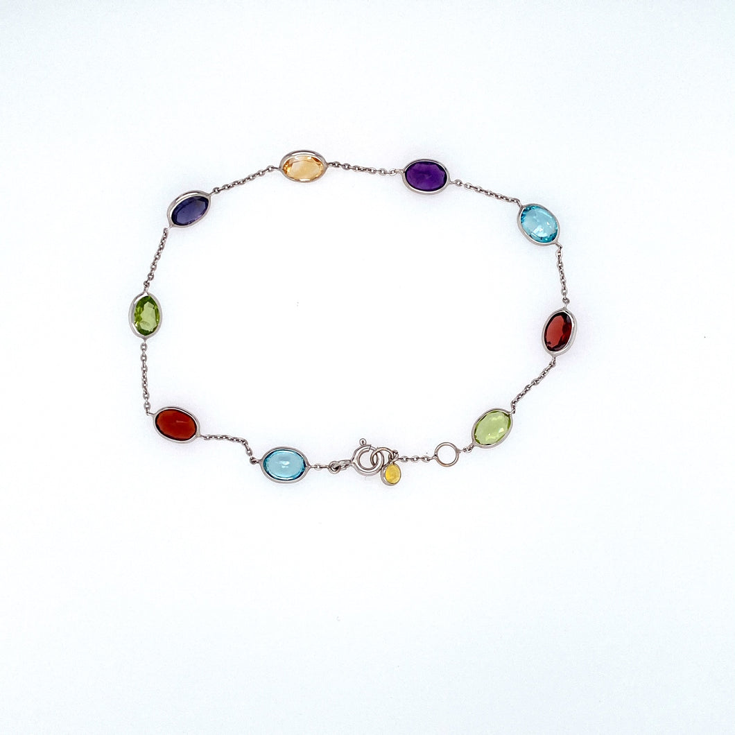Full of Color in this 14 Karat White Gold Bracelet Featuring 7.5ctw Bezel Set Semi Precious Gemstones Like Amethyst, Blue Topaz, Citrine, Garnet, and Peridot, The Bracelet is Secured with a White Gold Spring-ring Clasp. Total Length is 7 1/2