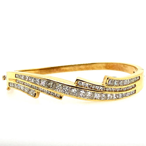 One of our favorite Hinged Bangles, This 14 Karat Yellow Gold Bangle Features Approximately 8.00 carats of SI Diamonds. Their is a safety 8 for added security.  Total Weight 62.8 Grams