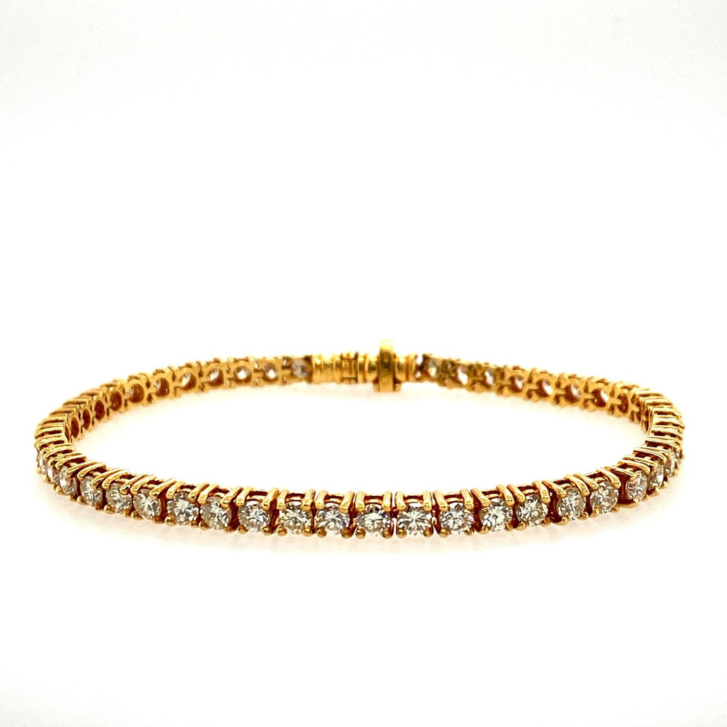 This Beautiful Tennis Bracelet has Approximately 5.00 Carats Total Weight of High Quality Brilliant-Cut Diamonds set into Luxurious 18 Karat Yellow Gold. A Hidden Safety is Provided for Extra Security.  Total Length is 7