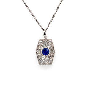 "Reminiscent of the Art Deco-Style, This 18 Karat White Gold Necklace, made by Kattan, Features a Beautiful Round .47 Carat Blue Sapphire Gemstone Bezel Set into the Center of  an Elongated Hexagon Shaped Pendant with a High Polished Bail. Set around the Pendant is a Total of .70 Carat Weight of Round and Baguette-Cut Diamonds.  The Pendant Hangs from a 18 1/2""  Karat White Gold Curb Link Chain.  Total Weight 5.7 Grams"