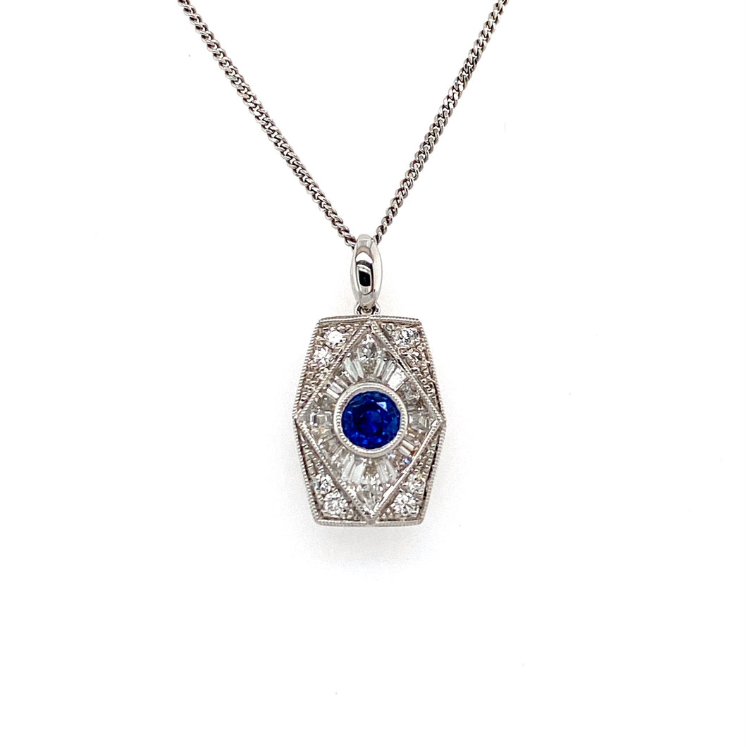 Reminiscent of the Art Deco-Style, This 18 Karat White Gold Necklace, made by Kattan, Features a Beautiful Round .47 Carat Blue Sapphire Gemstone Bezel Set into the Center of  an Elongated Hexagon Shaped Pendant with a High Polished Bail. Set around the Pendant is a Total of .70 Carat Weight of Round and Baguette-Cut Diamonds.  The Pendant Hangs from a 18 1/2