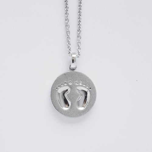 mommy chic baby's footprints round disc necklace in sterling silver.  can be worn at 18