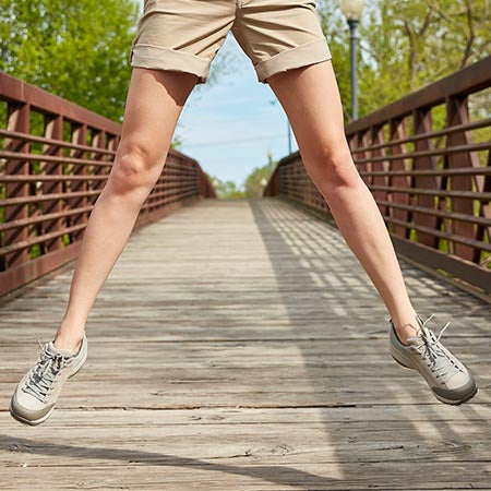 Active young woman jumping on a bridge