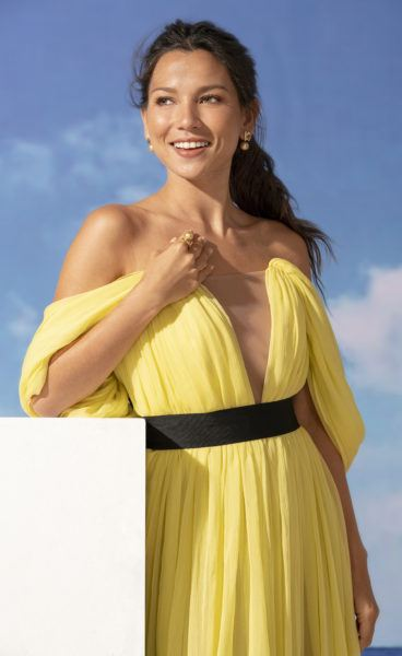 Woman in a yellow dress wearing pearl ring and pearl earrings.