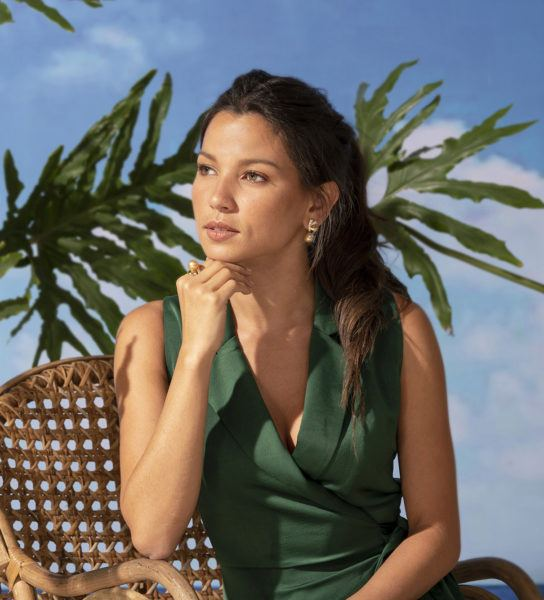 Woman in green dress wearing pearl earrings and pearl ring