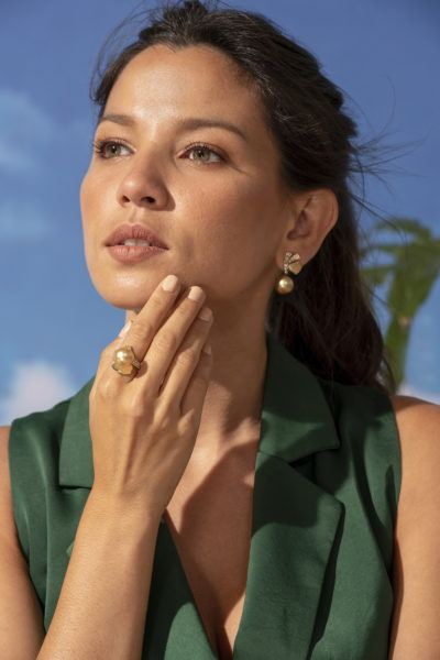 Woman in green wearing pearl earrings and pearl ring