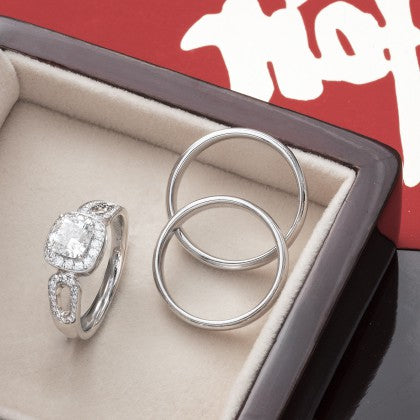 Engagement ring and wedding bands inside ring box