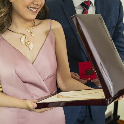 Chinese couple holding a red box with a necklace inside