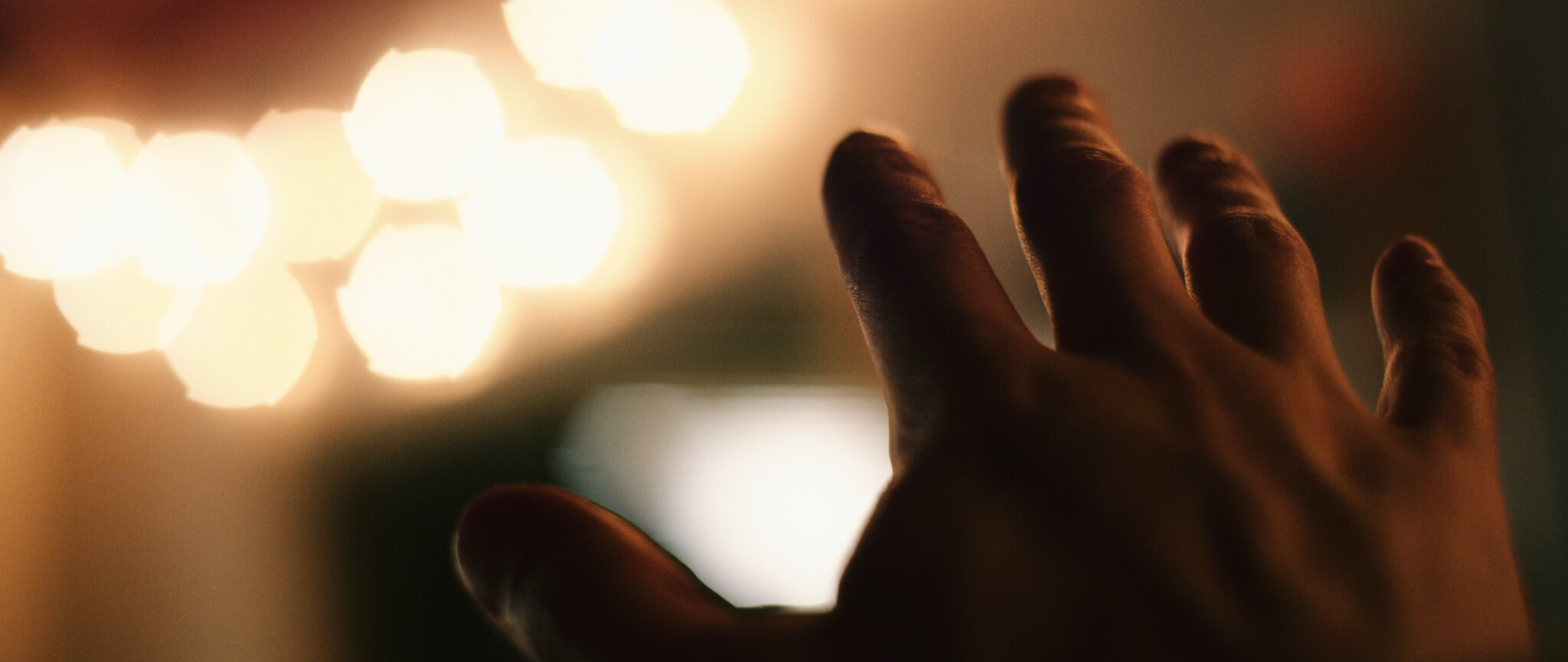 hand reaching out to lights with ninja star bokeh, taken on the Zeiss Contax lenses
