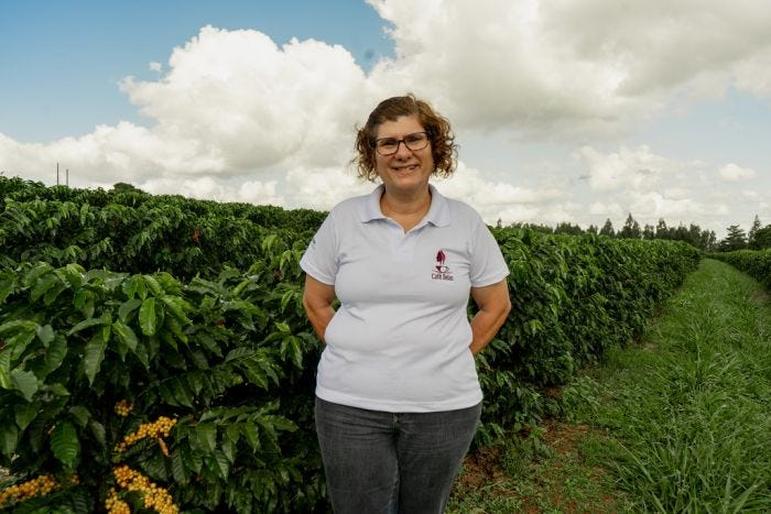 Brazilian Coffee Grower Arabela Pereira Lima proudly standing with her crops.