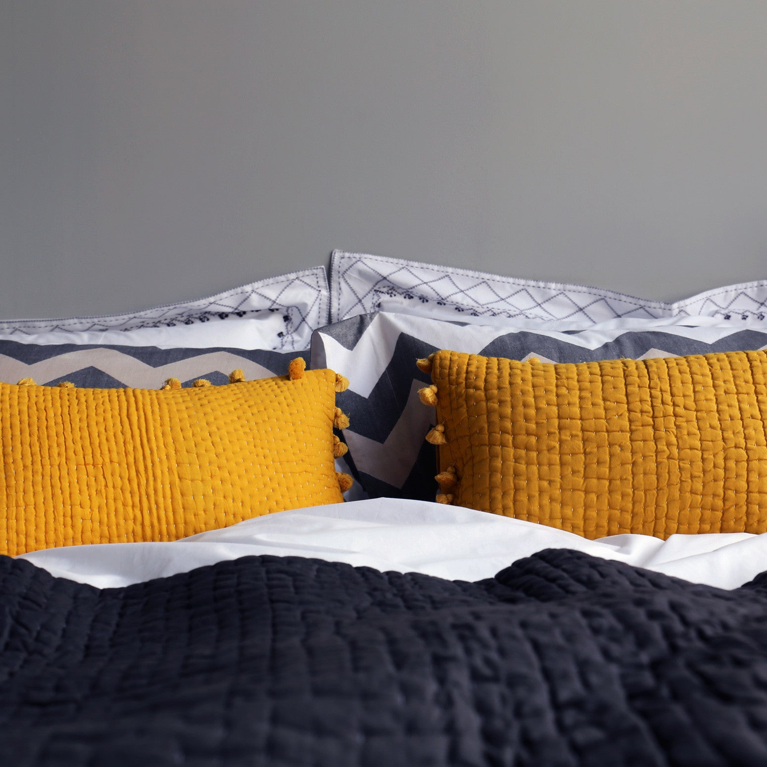 Yellow pompom quilted cushion