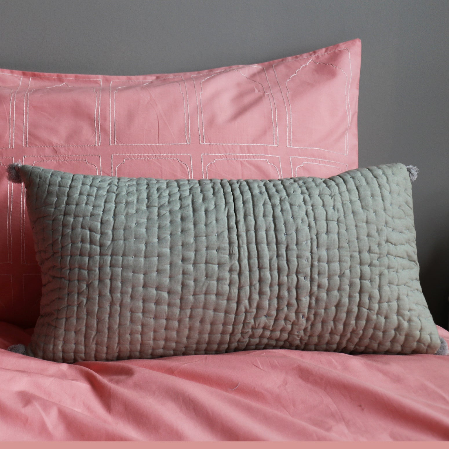 Grey pompom quilted cushion