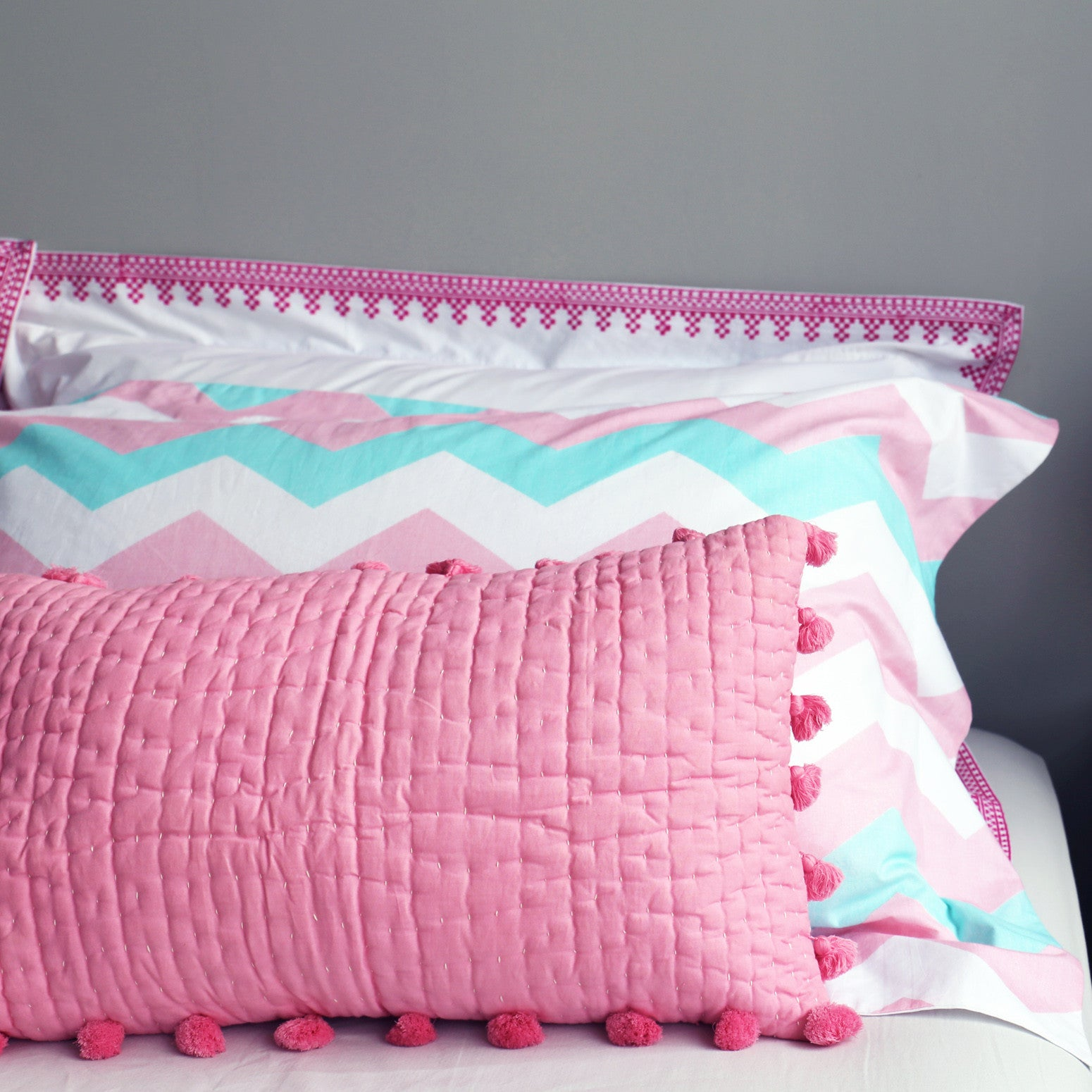 Pink pompom quilted cushion